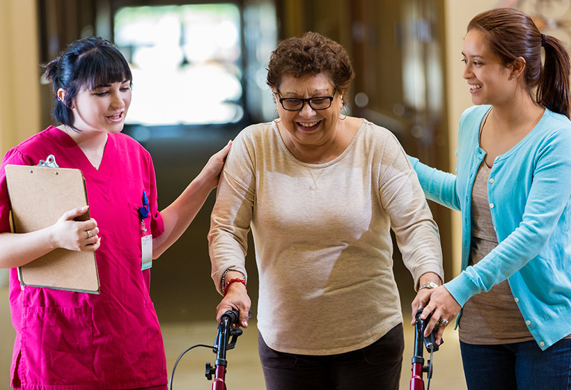 Senior woman walking and receiving assistance by caregivers
