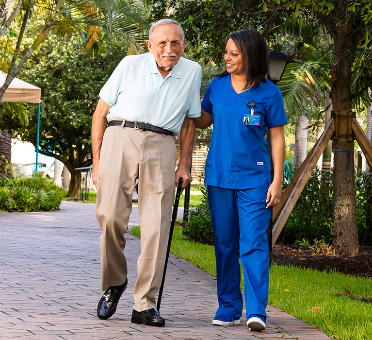 Resident walking outdoors with caregivers