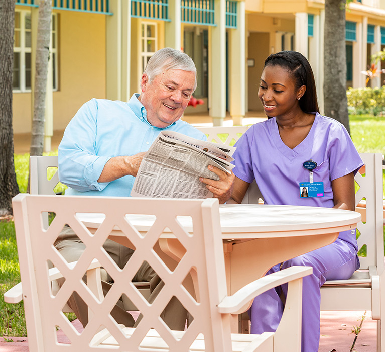 Resident reading the newspaper with assisted living nurse