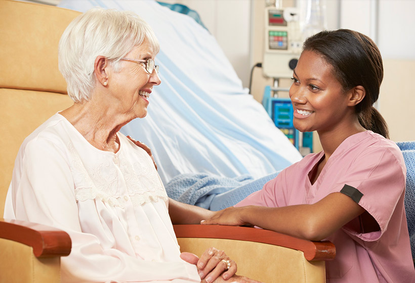 Senior receiving on-site treatment with caregiver
