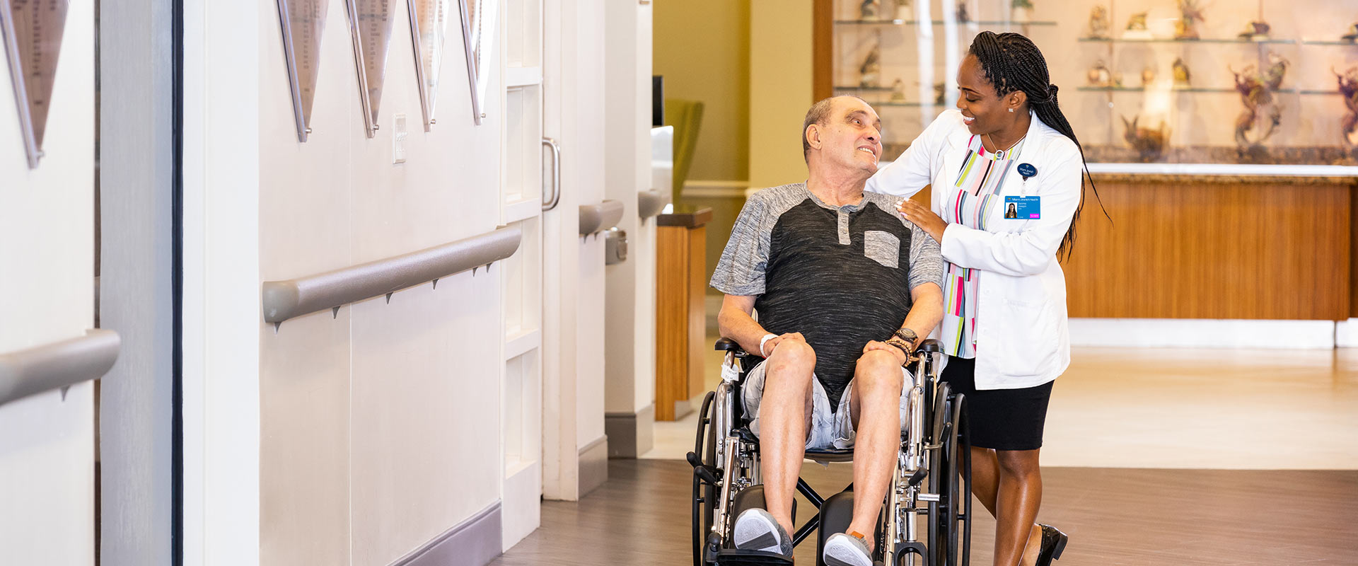 Man in wheelchair smiling at Nurse