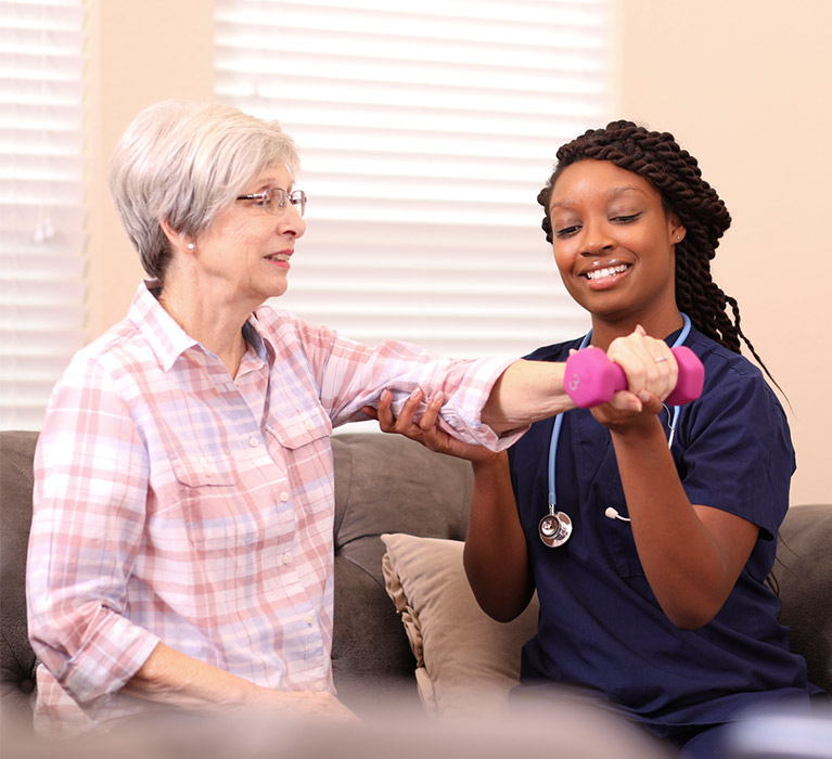 home health aides helping senior woman lift a dumbbell