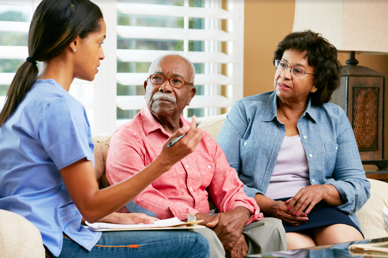 Caregiver giving assistance to elderly couple at home